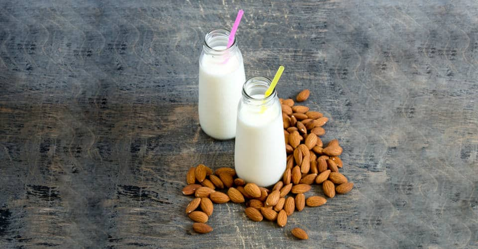 almond milk in bottle and almonds