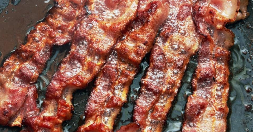 bacon slices being cooked in frying pan