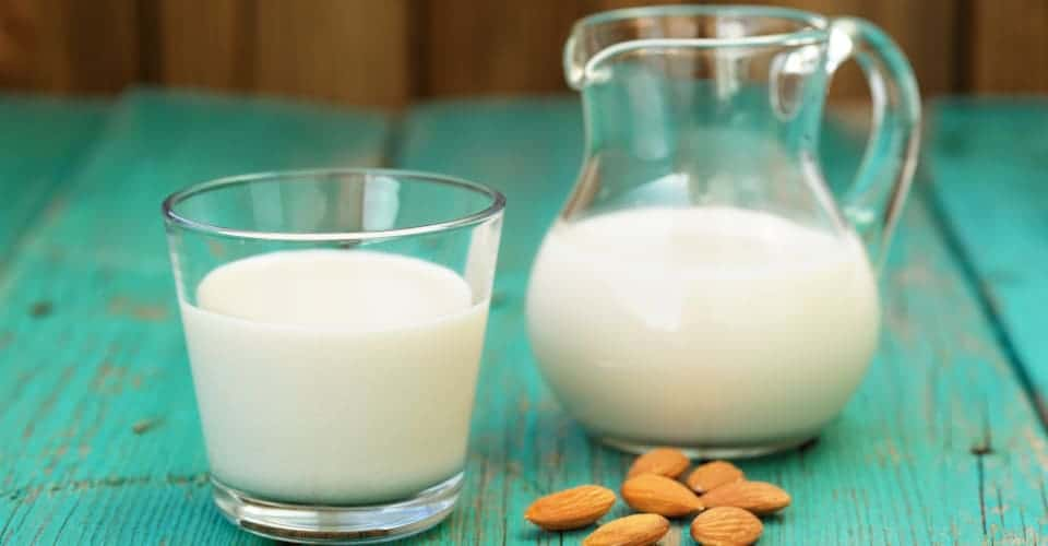 fresh almond milk in glass jar and glass bowl