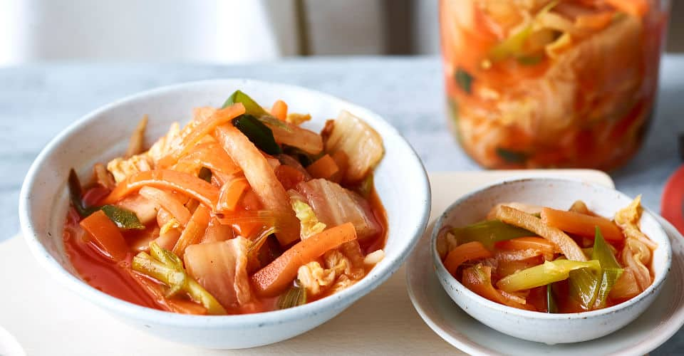 kimchi in bowls and bottle