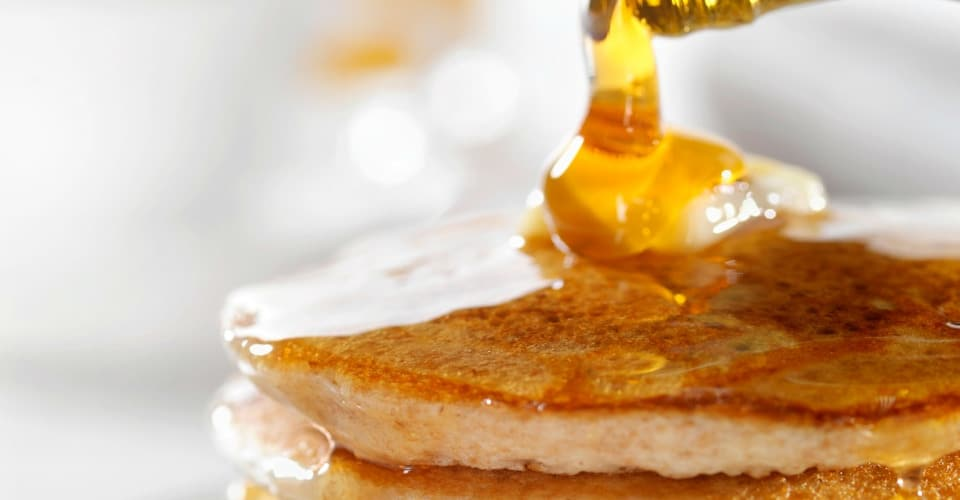 pouring maple syrup into pancake
