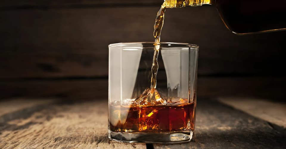 pouring rum into glass
