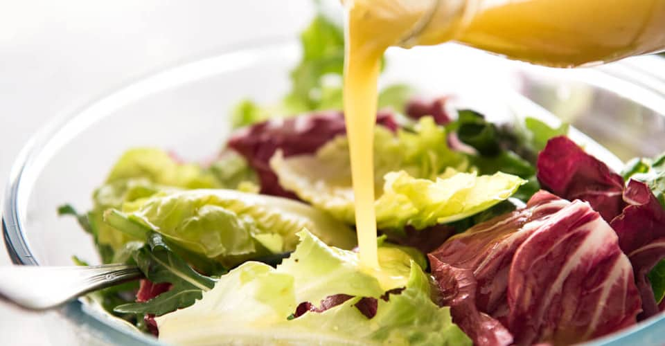 pouring salad dressing into salad
