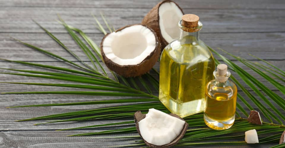 two bottles with coconut oil and some coconut shells
