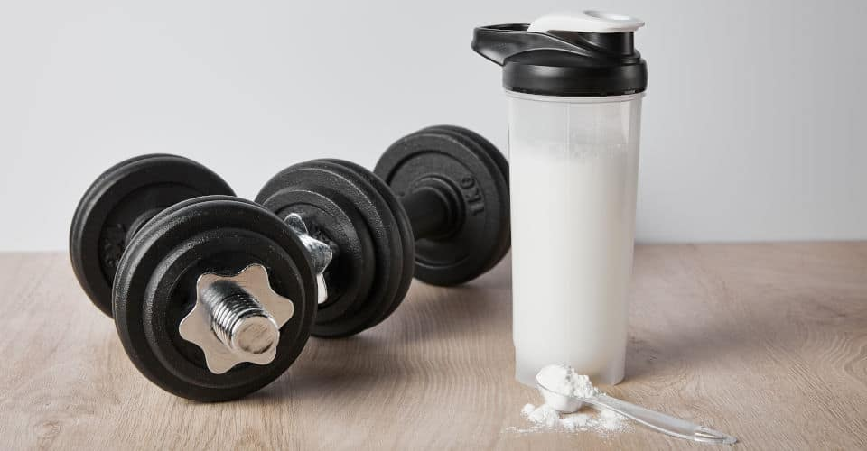 black dumbbells sports bottle and spoon of protein powder