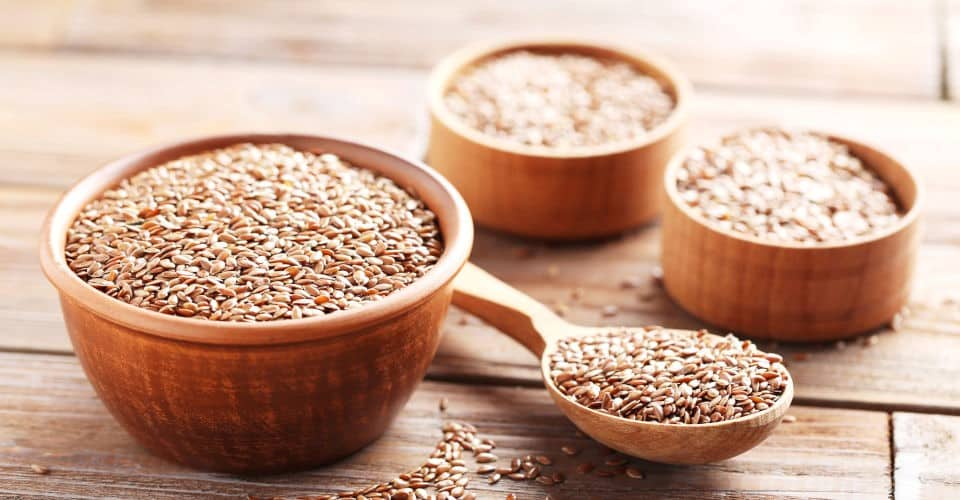 flax seeds in spoon and bowls