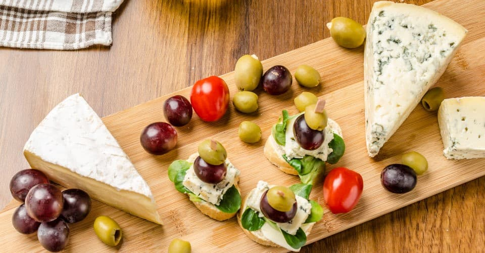 blue cheese with olives grapes and salad