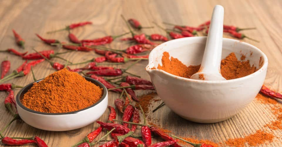 chili powder in mortar and pestle surrounded by chili pepper