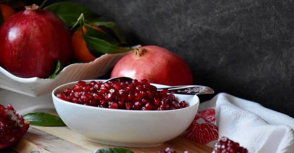 pomegranate seeds in bowl with spoon