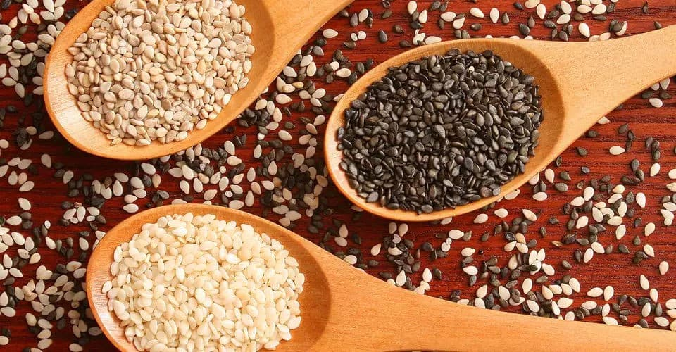 white and black sesame seeds in spoons